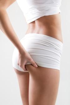 Portret van aantrekkelijke vrouw met perfect lichaam controleert cellulitis op haar billen