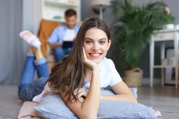 Portret van aantrekkelijke vrouw ontspannen op de vloer met wazig man op de achtergrond.