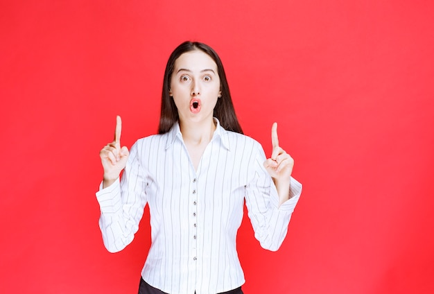 Portret van aantrekkelijke vrouw permanent en wijzende vingers tegen de rode muur.