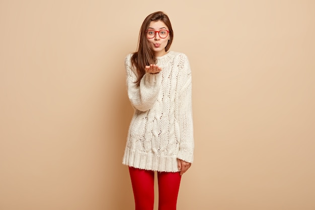 Portret van aantrekkelijke vrouw stuurt luchtkus, houdt de handpalmen naar voren gestrekt, draagt witte wintertrui, rode legging, drukt liefde uit, heeft getuite lippen, toont gebaar van groet of afscheid
