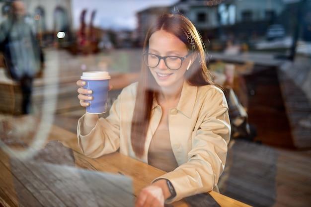Portret van aantrekkelijke vrouwelijke fotograaf journalist in brillen met rood haar zittend in café werken met digitale netbook computer, op afstand werken met mediabestanden. foto door raam