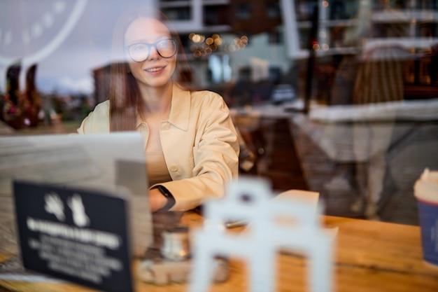 Portret van aantrekkelijke vrouwelijke fotograafjournalist met rood haar die in café zit te werken