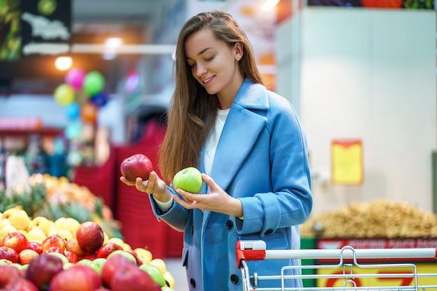Portret van aantrekkelijke vrouwenkoper met kar in de kruidenierswinkelwinkel tijdens het kiezen van en het kopen van verse appelen bij fruitafdeling