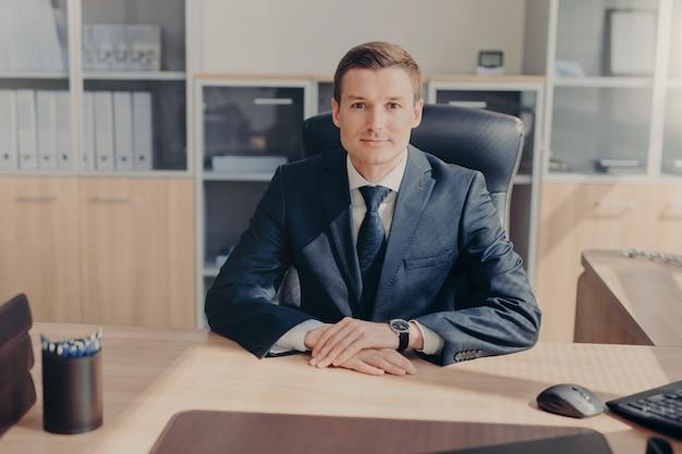 Portret van aantrekkelijke welvarende zakenman draagt zwart pak, wit overhemd met stropdas