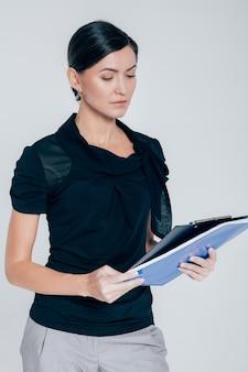 Portret van aantrekkelijke zaken vrouw met een map met documenten op een grijze achtergrond