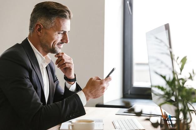 Portret van aantrekkelijke zakenman 30s dragen pak met behulp van mobiele telefoon tijdens het werken op de computer op kantoor