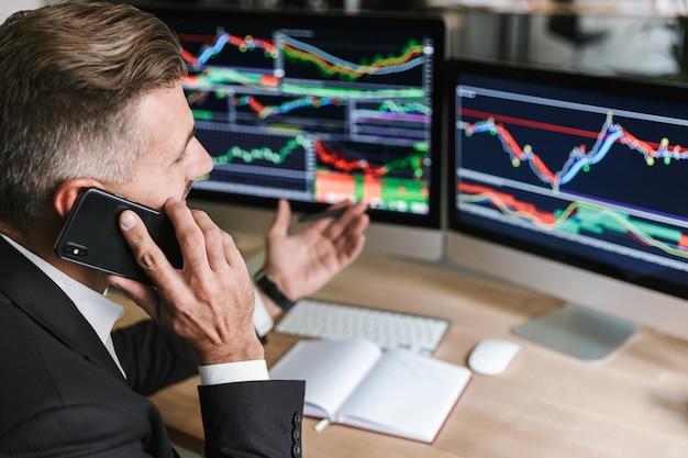 Portret van aantrekkelijke zakenman 30s dragen pak spreken op mobiele telefoon tijdens het werken met digitale afbeeldingen op computer in kantoor