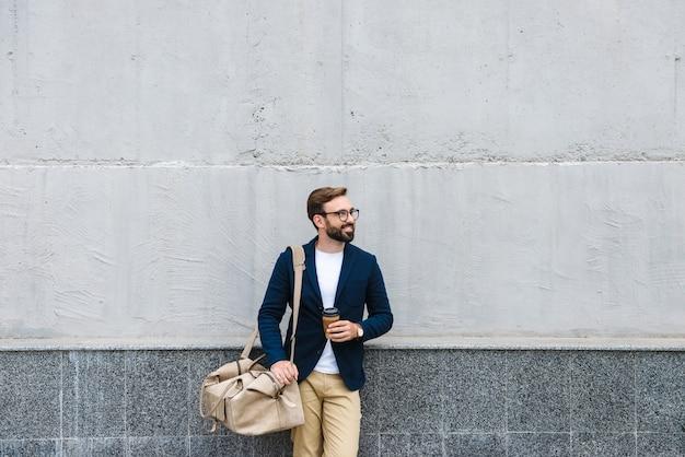Portret van aantrekkelijke zakenman die een bril draagt die een papieren beker en een draagtas houdt terwijl hij in de buurt van de muur staat