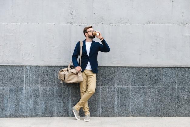 Portret van aantrekkelijke zakenman die een bril draagt die koffie drinkt uit een papieren beker en draagtas terwijl hij in de buurt van de muur staat