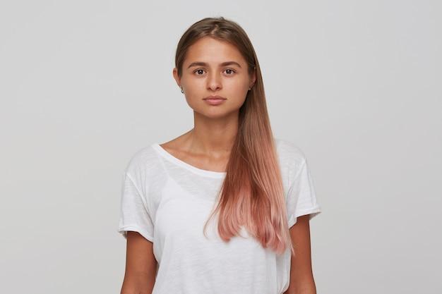 Portret van aantrekkelijke zelfverzekerde jonge vrouw met lang geverfd pastel roze haar draagt t-shirt staande over witte muur met copyspace voor uw reclame kijkt naar de voorkant