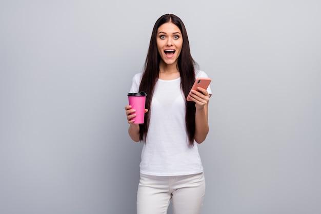 Portret van aardig aantrekkelijk verbaasd meisje dat in handen houdt die cel gebruiken die latte drinkt