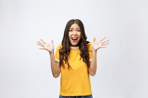 Portret van aardig geschokt positief schattig jong meisje in casual geel overhemd