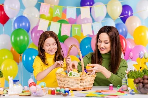 Portret van aardige aantrekkelijke mooie charmante creatieve vrolijke vrolijke meisjes die met de hand gemaakt ambachtelijk kunstwerk voorbereiden van het dessertmandje van het kleine zusje tijdverdrijf
