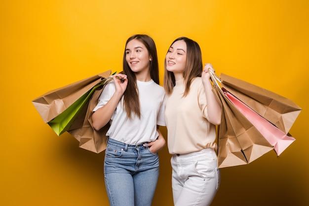 Portret van aardige aantrekkelijke mooie meisjes die kleurrijke zakken dragen die pret hebben die op gele kleurenmuur wordt geïsoleerd