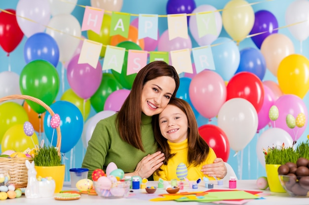 Portret van aardige aantrekkelijke mooie tedere vrolijke meisjes die het voorbereiden van ambachten handgemaakte chocolade-eieren maken die kleine kleine roodharige zus omhelzen