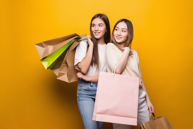 Portret van aardige leuke meisjes die bedrijf in handen omhelzen die nieuwe koele aankoop dragen die op gele muur wordt geïsoleerd