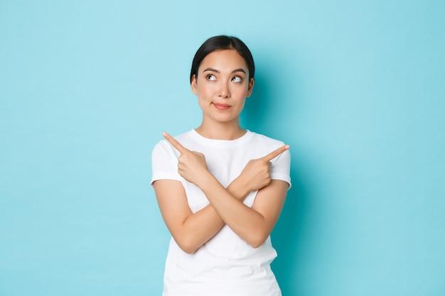 Portret van aarzelend schattig aziatisch meisje in casual wit t-shirt, nieuwsgierig kijkende linkerbovenhoek terwijl zijwaarts wijst, keuze maken, besluiteloos over blauwe muur staan, beslissen