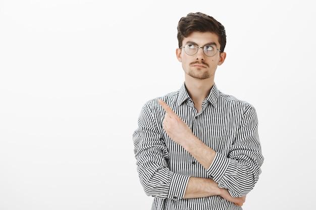 Portret van aarzelende, geïntrigeerde kalme man met baard en snor in ronde bril, kijkend en wijzend naar de linkerbovenhoek met een nieuwsgierige uitdrukking, iets interessants over grijze muur zien