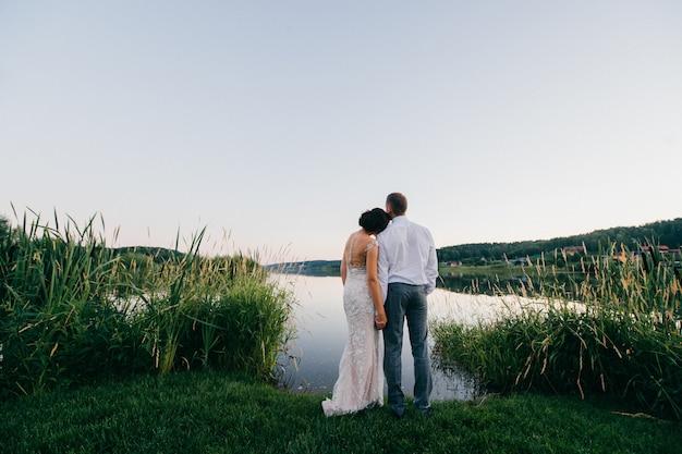 Portret van achter van bruidspaar dat meer in avond bekijkt