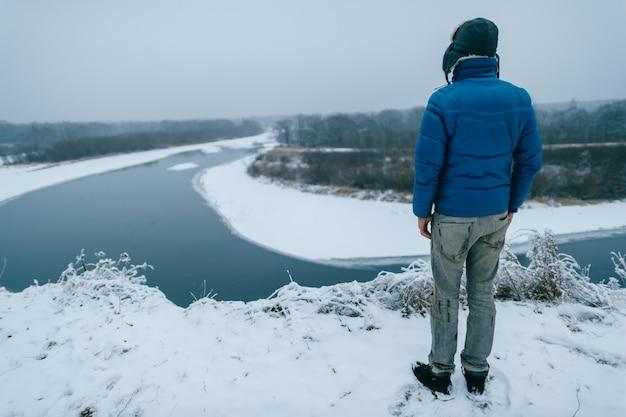 Portret van achteren van een man in de winterkleren die zich op de rand van een heuvel bevinden en de winter sneeuwrivier bekijken.