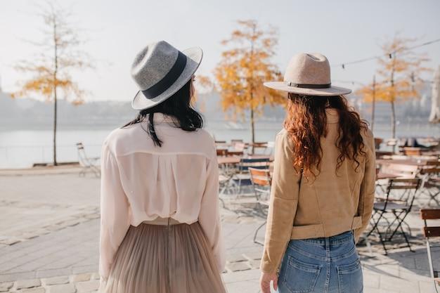 Portret van achterkant brunette vrouw in hoed praten met vriend over aard