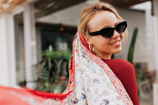 Portret van achterkant van lachende vrouw met zwarte zonnebril en sjaal in het hoofd