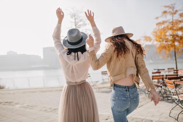 Portret van achterkant van romantische brunette vrouw dansen met handen omhoog op natuur muur