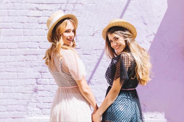 Portret van achterkant van twee zalige meisjes die handen houden en over schouder kijken