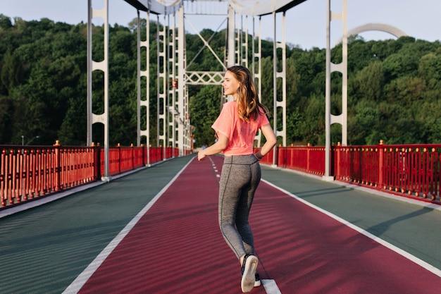 Portret van achterkant van vrolijk meisje loopt in de ochtend en geniet van uitzicht op de natuur. buitenfoto van geïnspireerde dame die oefening doet.