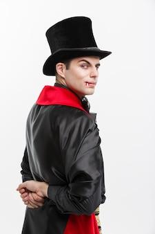 Portret van achtermening knappe kaukasische vampier in zwart en rood halloween-kostuum.