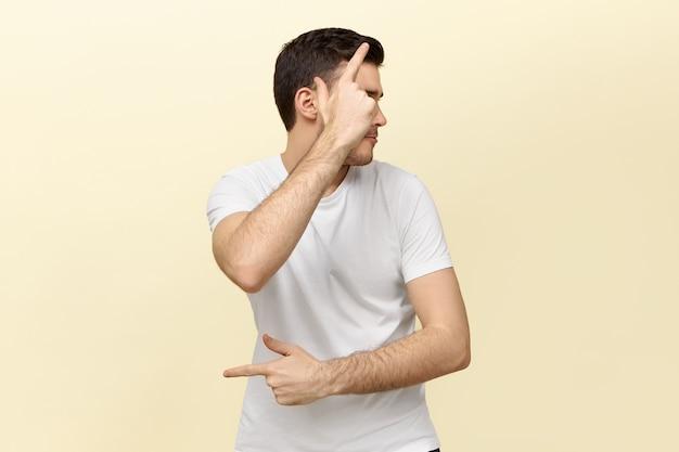 Portret van actieve, energieke jongeman die pret maakt gebaren alsof hij een pistool vasthoudt
