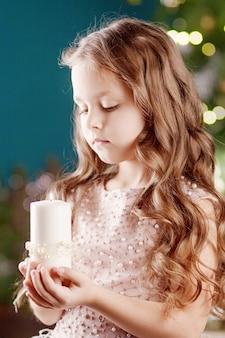 Portret van acute langharige meisje in jurk met lichten. meisje bedrijf brandende kaars. kerstmis, nieuwjaar en verjaardagsviering concept. kerstvakantie. kopieer ruimte