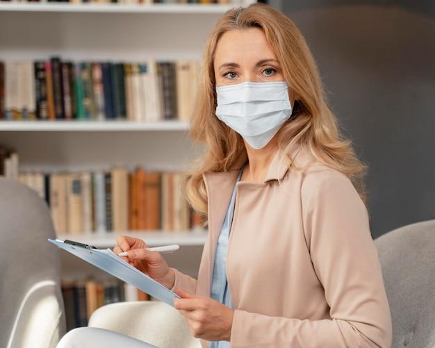 Portret van adviseur met masker in therapiekantoor