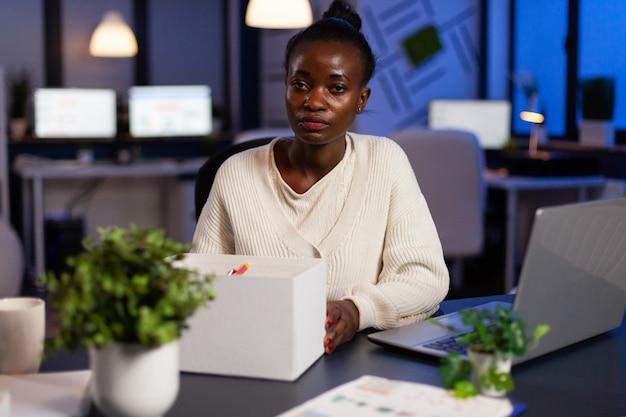 Portret van afgetreden ontslagen afro-amerikaanse zakenvrouw die objecten inpakt