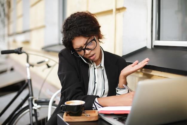 Portret van african american girl in glazen aan de tafel zitten en emotioneel praten over haar mobiel