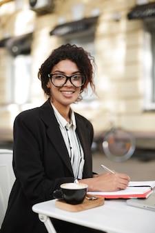 Portret van african american girl in glazen zitten aan de tafel van café en gelukkig