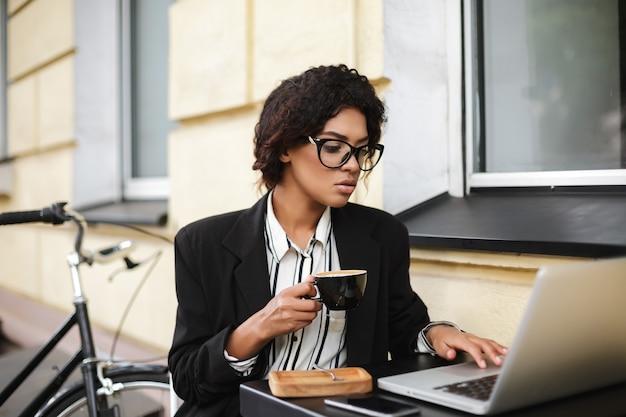 Portret van african american girl in glazen zittend aan de tafel van café met kopje koffie in handen