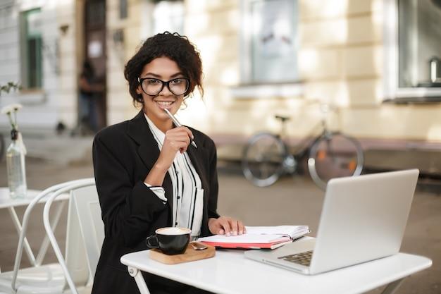 Portret van african american girl, zittend aan de tafel van café en gelukkig