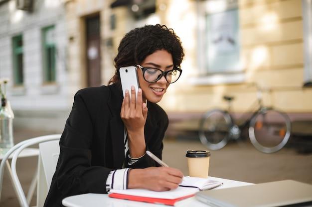 Portret van african american girl, zittend aan de tafel van café en schrijven in haar notitieblok tijdens het praten op mobiel