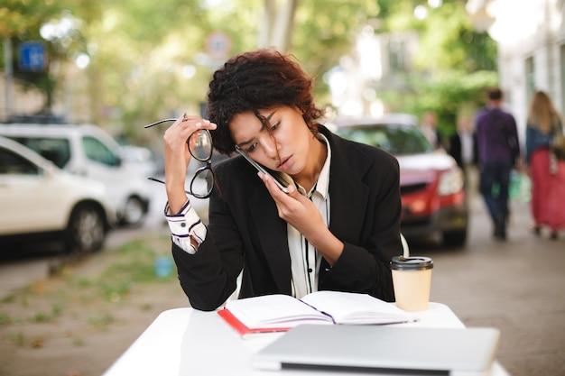 Portret van african american girl, zittend aan tafel met een bril in de hand en moe