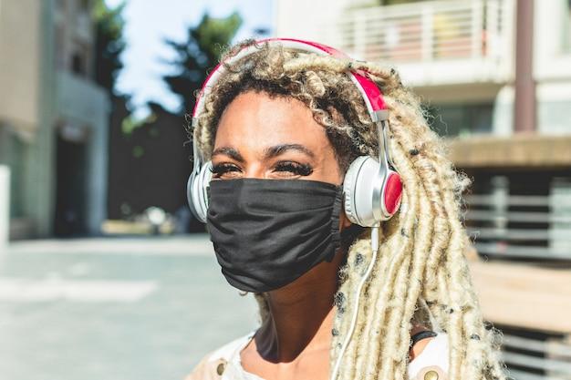 Portret van afrikaans meisje die blonde dreadlocks haar het luisteren muziek bewegen terwijl het dragen van gezichts beschermend masker voor coronavirus-preventie