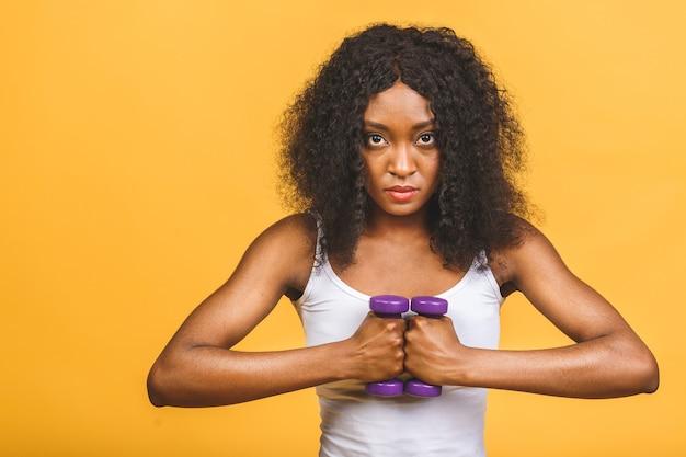 Portret van afrikaanse amerikaanse vrouw die haar spier met domoren uitoefent