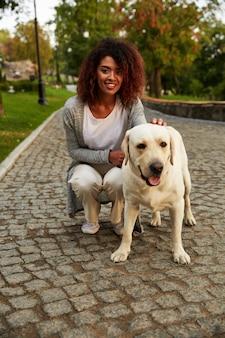 Portret van afrikaanse dame die met hond in park loopt