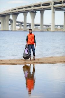 Portret van afrikaanse jonge man die met vuilnis aan de oever van de rivier met grote brug