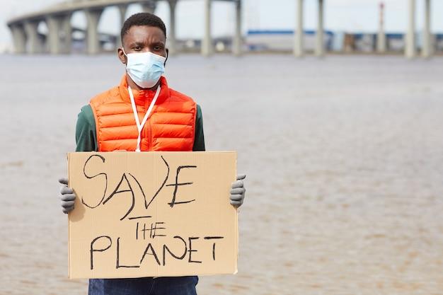 Portret van afrikaanse jonge man in beschermend masker met plakkaat terwijl hij in de buurt van de kustlijn staat