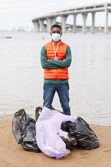 Portret van afrikaanse jonge man in beschermend masker staande met gekruiste armen in de buurt van de vuilniszakken in de buurt van de kustlijn