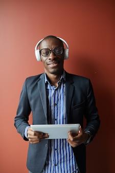 Portret van afrikaanse jonge man in brillen en draadloze koptelefoon glimlachend in de camera tijdens het gebruik van tablet-pc tegen de bruine achtergrond