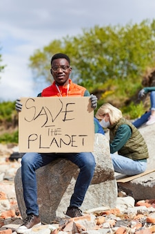 Portret van afrikaanse jonge man plakkaat houden en camera kijken zittend op de steen buitenshuis