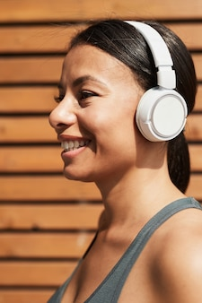 Portret van afrikaanse jonge vrouw in draadloze koptelefoon luisteren naar muziek en glimlachen tijdens het trainen...