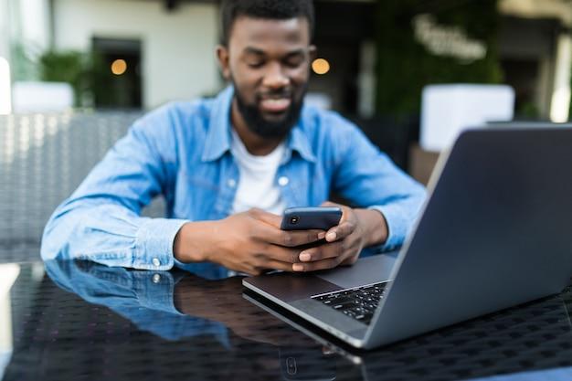 Portret van afrikaanse man praten aan de telefoon met laptop voor hem op tafel in café